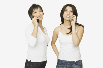 Studio shot of Asian mother and adult daughter talking on cell phones