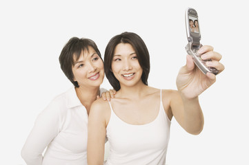 Studio shot of Asian mother and adult daughter talking self portrait