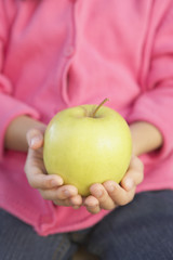 Close up of a young girl holding a green apple