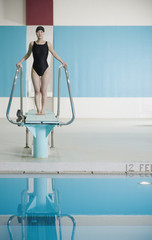 Female Asian swimmer on diving board