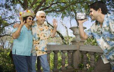 Young man using video camera to film senior couple waving