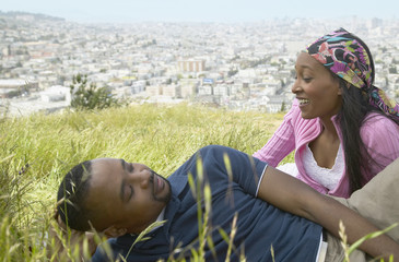African couple sitting in grass on hill above city
