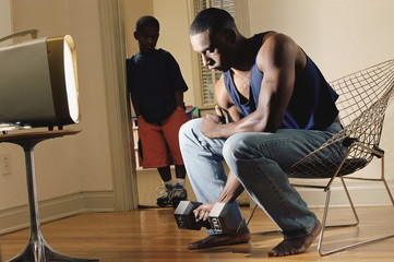 African man lifting dumbbell while son watches