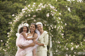 Hispanic bride with mother and young girl smiling