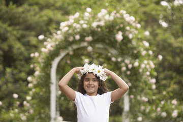 Young Hispanic girl with flower garland on head