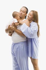 Studio shot of parents smiling at baby