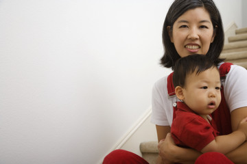 Portrait of Asian mother holding baby