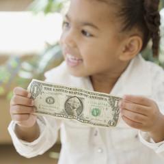 African girl holding dollar bill