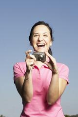 Portrait of Hispanic woman holding camera