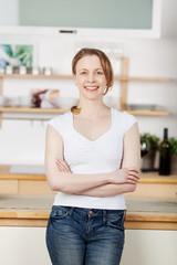 junge lächelnde frau steht in der küche