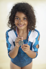 Young female gymnast wearing medal