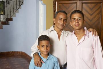 Hispanic father and sons hugging