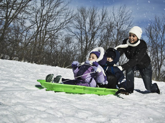 Mother pushing children on sled