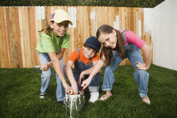 Mixed Race children painting fence