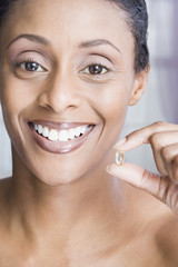 African American woman holding vitamin