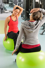 Senior woman with trainer stretching fitness ball