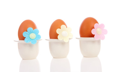 Three chicken eggs in holder with flowers