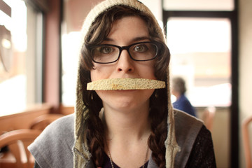 Woman with cantaloupe in her mouth at a restaurant.
