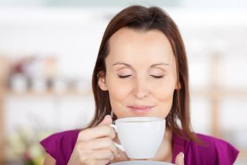 frau genießt kaffee mit geschlossenen augen