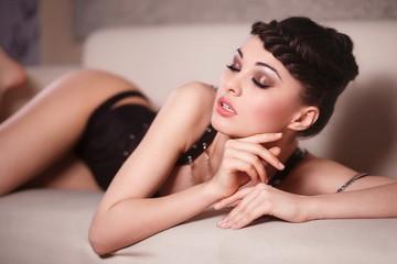 Beautiful sexy fashion girl in black corset lying on the sofa