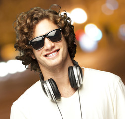 portrait of young man with headphones at city by night