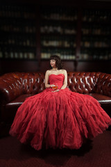 Woman in red evening dress sitting on the sofa