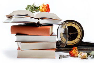A stack of books and antique clock on a white background.