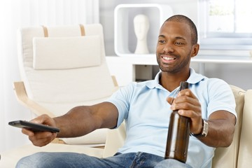 Man with beer and remote control