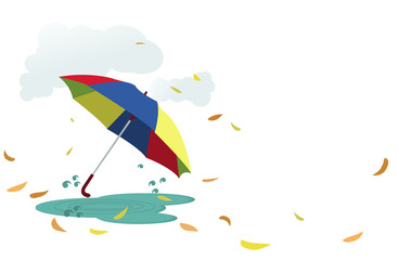 Umbrella with autumn leaves around it and clouds