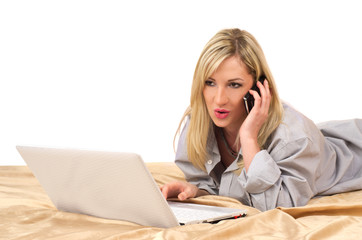 Blonde woman working with laptop on bed