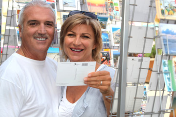 Mature couple looking at postcards