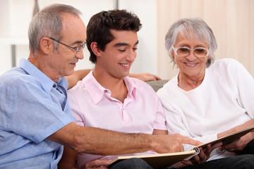 Grandparents and grandson watching photo album