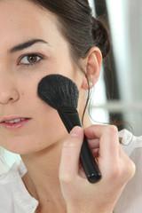 Woman applying blush on her cheeks