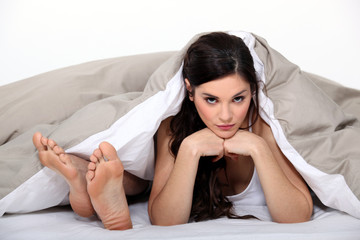 Male feet and head of a woman in bed
