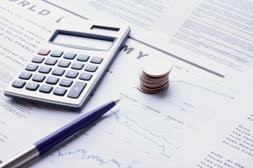 pen, coins and calculator on business paper