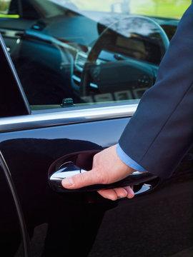 Businessman's hand opening door of his luxury car