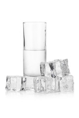 Frozen glass of iced vodka with ice cubes on white background