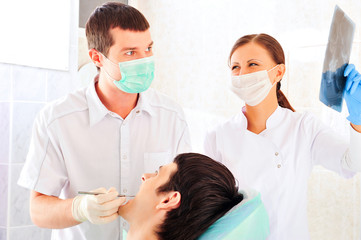 A dentist and a nurse curing young man`s teeth