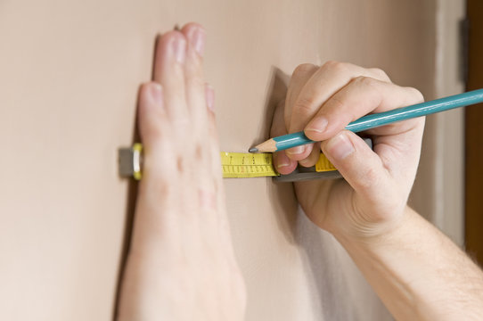 measuring with tape measure on wall