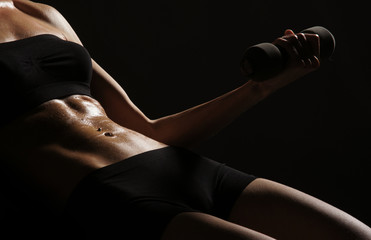 Sexy belly of a young and fit woman on a black background
