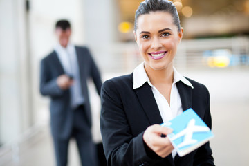 attractive businesswoman handing over air ticket at airport