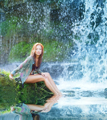 A young redhead woman posing near a waterfall