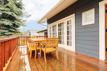 Wood deck with furniture and grey house.