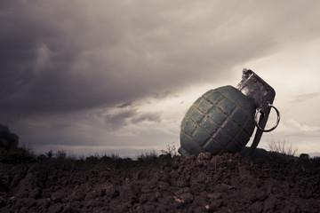 green grenade on a battlefield at dusk