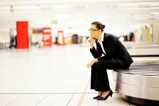 businesswoman waiting for her luggage at airport.