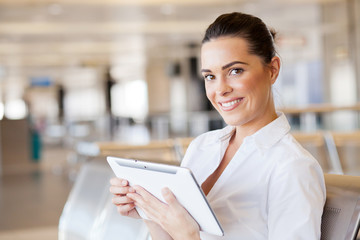 happy young woman using tablet computer at airport