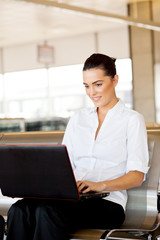pretty businesswoman using laptop at airport