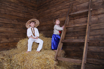two kids in traditional eastern european clothes on hayloft