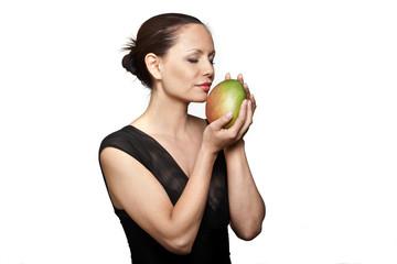 Portrait of beautiful woman smelling mango