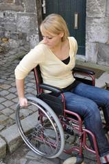 Rollstuhlfahrerin an Bordsteinkante
